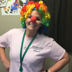 Staff member smiling with a clown wig and nose on her