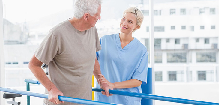 A rehabilitation staff member assisting a patient with walking safely on the parallel bars.