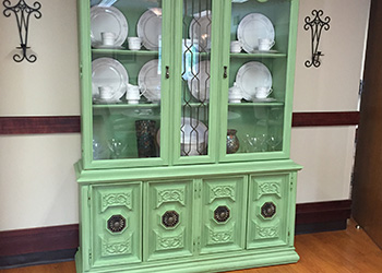 A china cabinet with glass doors displaying the china inside.