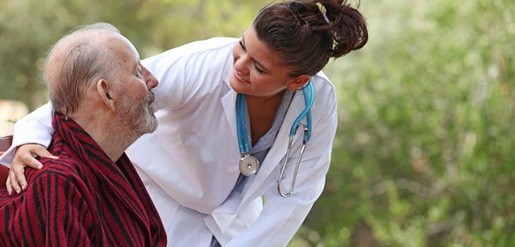 A nurse leaning in to talk to a patient.