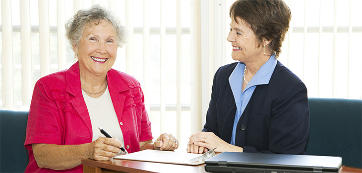 Two women in an office filling out paperwork together.