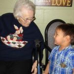 resident smiling with her grand son at the facility