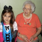resident smiling with her grand daughter at the facility
