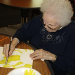 resident painting a flower at the facility