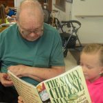 resident and great grand child reading together