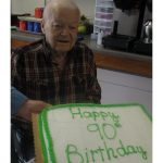 resident smiling with his 90th birthday cake