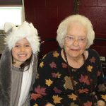 resident sitting with her great grand daughter as he is dressed up for halloween