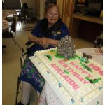 resident sitting with her birthday cake smiling