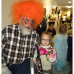 resident sitting with his great grand daughter as he is dressed up for halloween