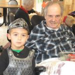 resident sitting with his great grandson as he is dressed up for halloween