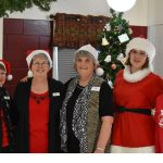 facility employees smiling together around the christmas tree