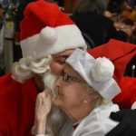 resident smiling with santa at the christmas party