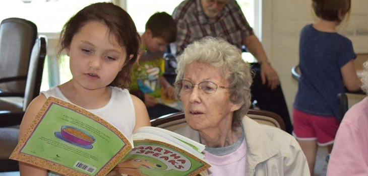 elderly women and her grand daughter reading books together at the facility