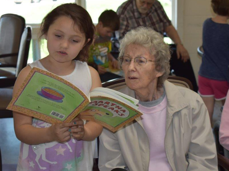 resident and visitor reading together