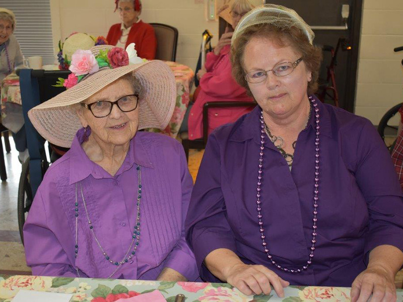 residents smiling together in hats