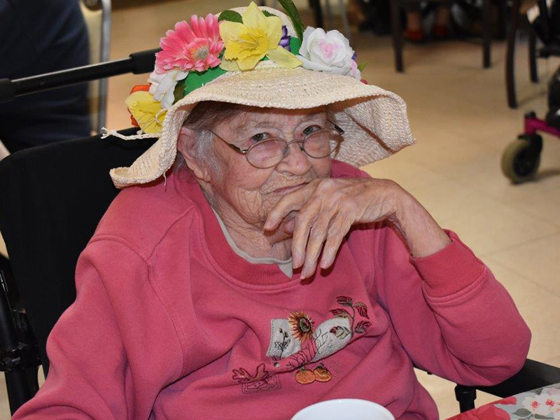 resident smiling with a funky hat on