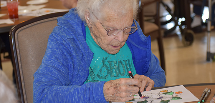 elderly women drawing a picture of a flowers with markers
