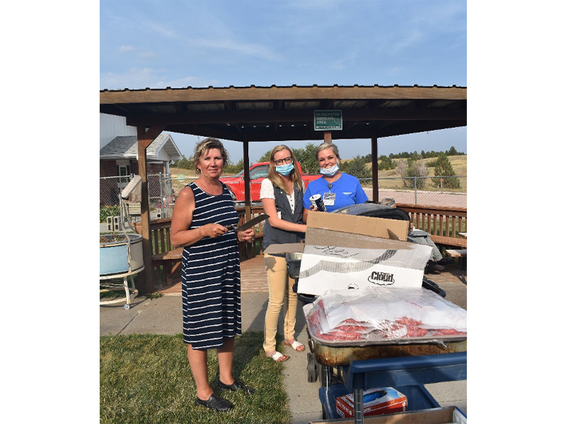 Employees cooking outdoors for residents.