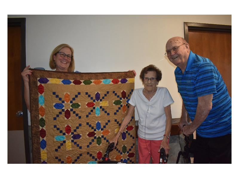 A family together holding up a quilt.