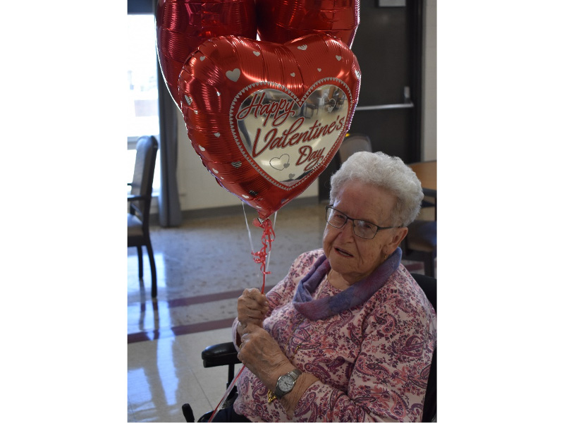 A resident holding a Valentine's Day balloon