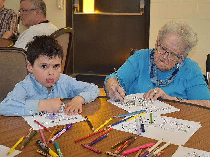 Pioneer Manor resident activity with boy coloring