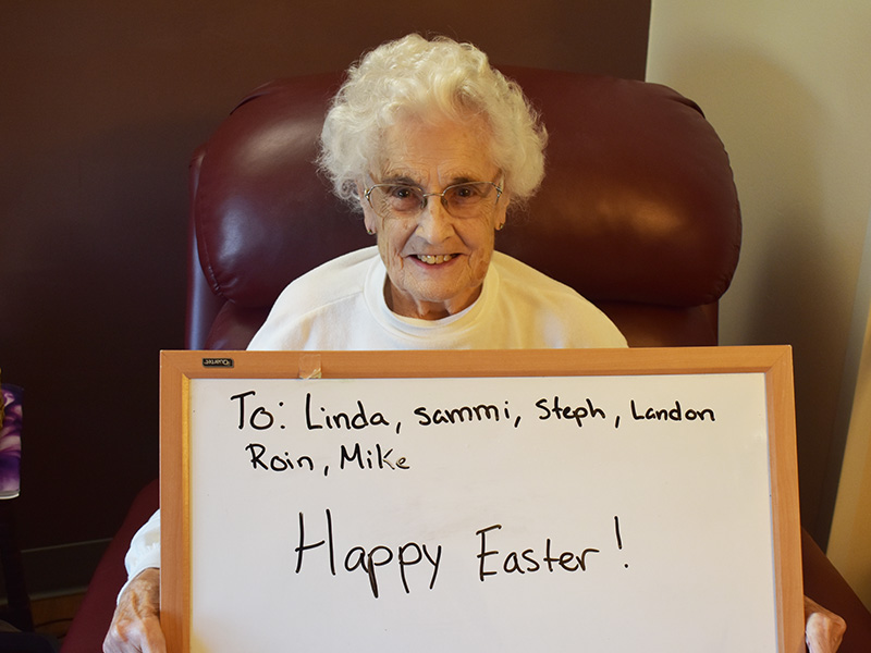 """Pioneer Manor happy resident with a white board saying """"Happy Easter."""""""