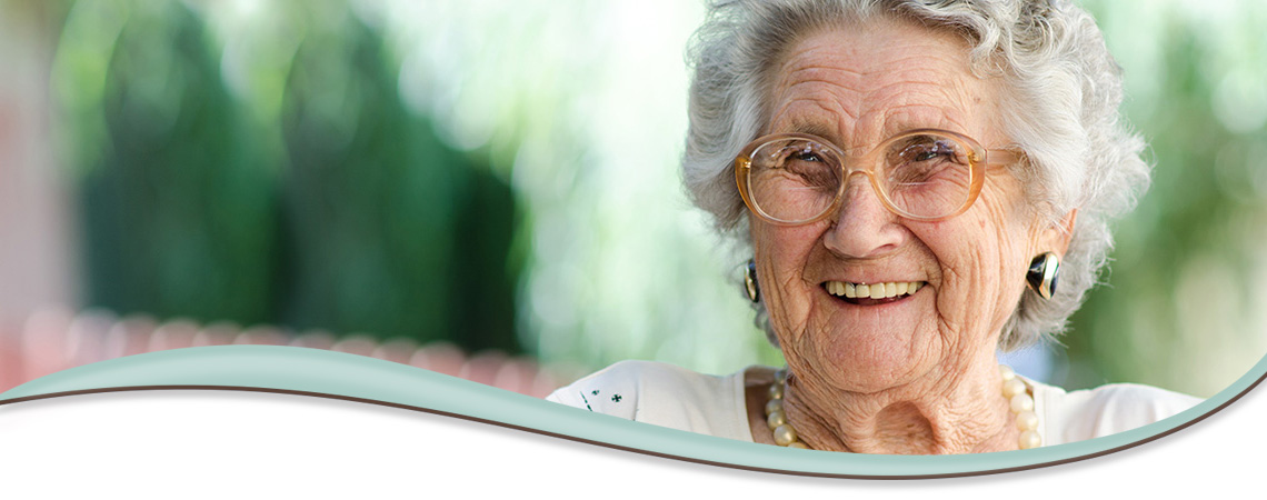 smiling elderly woman wearing glasses and pearls
