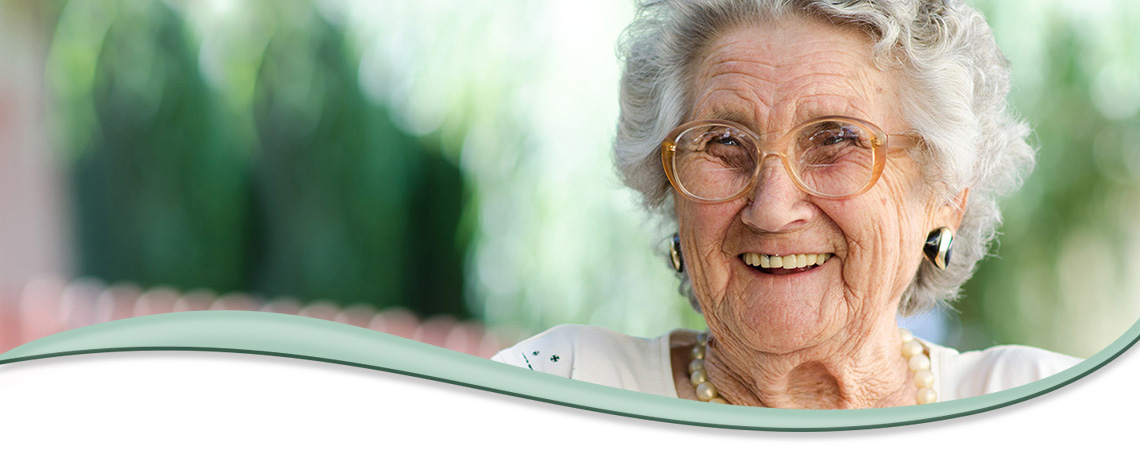 elderly woman smiling while wearing glasses and pearls