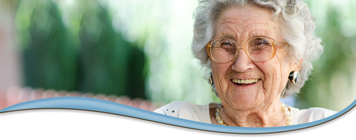 smiling elderly woman seating outside with greenery in the background