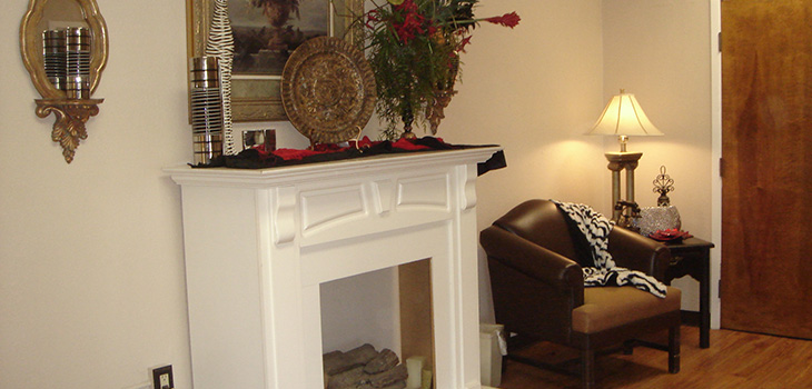 cozy sitting area with fireplace and an artful display on the mantle