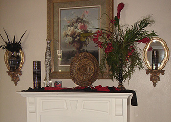 beautiful mantle with large floral arrangement, 2 side mirrors, artifacts and a painting