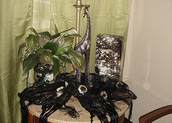 display on table of a giraffe figurine, live plant and a decorative scarf