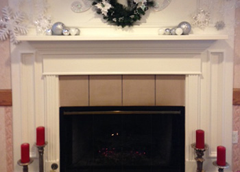 Christmas mantle display of silver and white with snowflakes and greenery