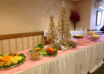 buffet table with fresh fruit, Christmas trees and desserts