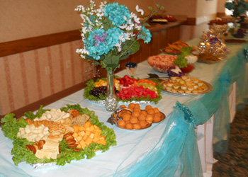 pretty buffet table with flowers, cheese platter, quiches, and blue tulle draping