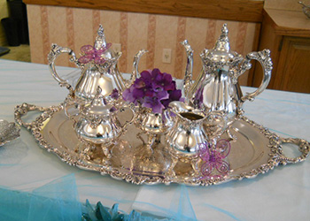 ornate silver tea and coffee set with a small vase and purple flowers