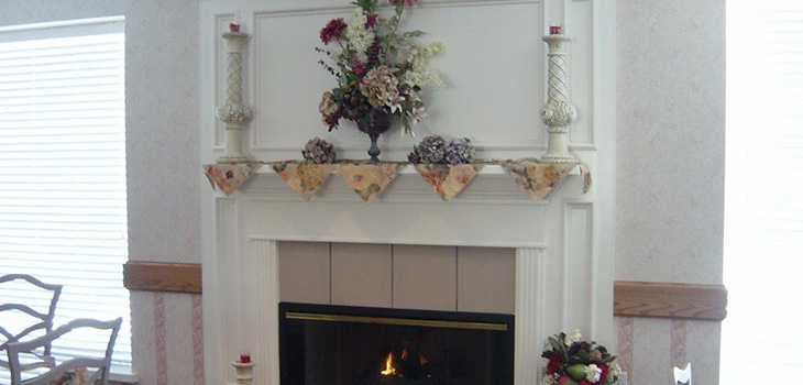 fireplace mantle with candles and flowers