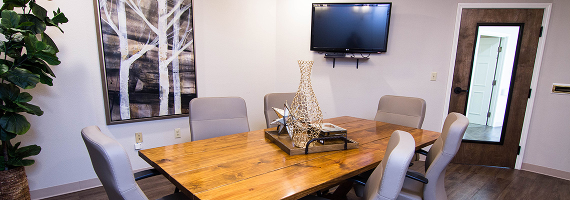 Nicely appointed meeting room with modern decor, live plants, and a TV mounted on the wall