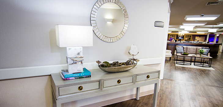 Side table with decorative books and a stylish mirror