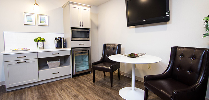Kitchenette with a bistro table and flat screen TV mounted on the wall
