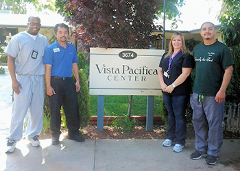vista pacifica sign surrounded by employees