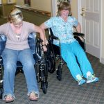 Two staff members racing in a wheel chair