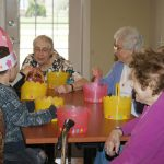 Residents and children sitting together looking at egg baskets