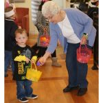 A resident placing an egg in a child's easter basket