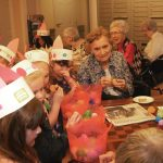 Children opening eggs with residents