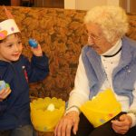 Child shaking an egg with a resident