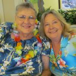 Resident and staff member dressed up Hawaiian style