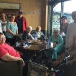 Residents and staff in a suite watching the Slammers baseball game