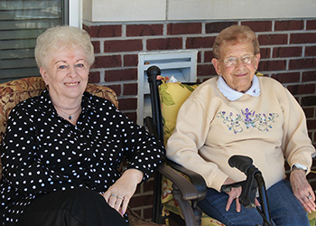 Two residents sitting outside enjoying the sunshine