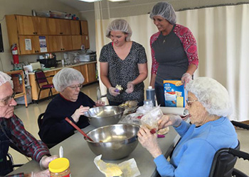 resident and nurses cooking together
